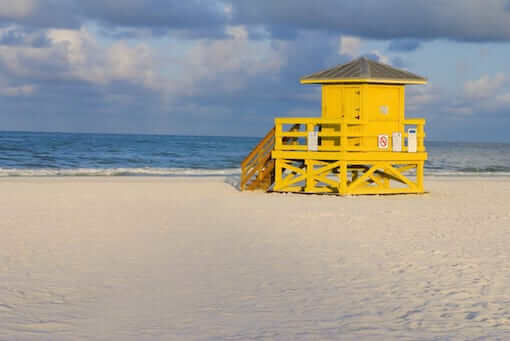 A yellow wooden lifeguard hut on an empty morning beach